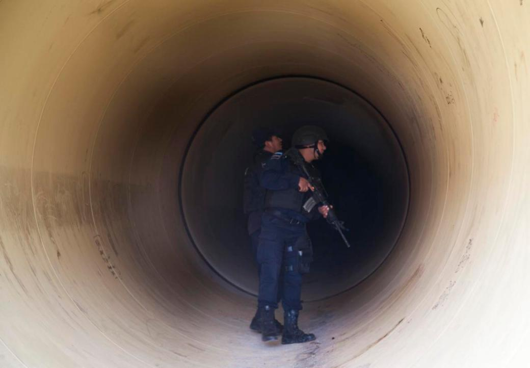 "Federal police inspect a drainage pipe outside the Altiplano maximum security prison in Almoloya, west of Mexico City, Sunday, July 12, 2015. Mexico's most powerful drug lord, Joaquin ""El Chapo"" Guzman, escaped from a maximum security prison through a tunnel that opened into the shower area of his cell, the country's top security official announced. (AP Photo/Marco Ugarte)"